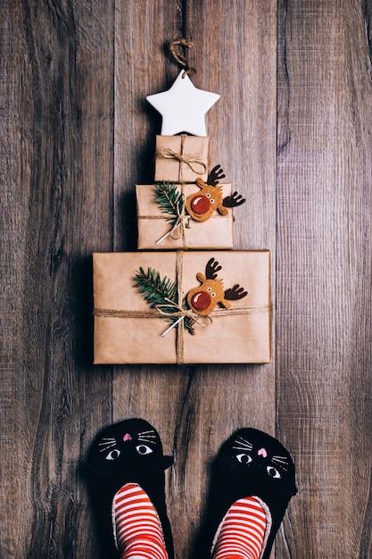 Trois cadeaux enveloppés dans du papier brun disposés en forme de sapin de noël avec une étoile sur le dessus. pieds de femme en chaussons de chat, chaussettes rayées. Photo Premium