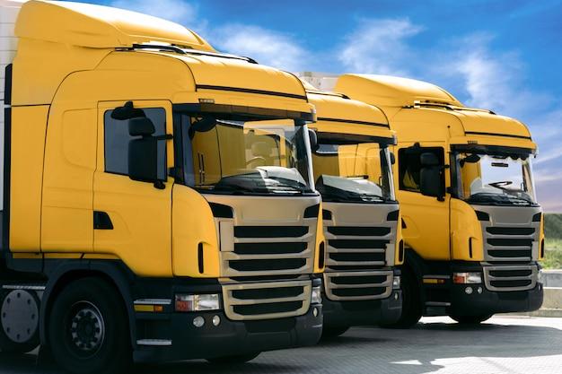 Trois Camions Jaunes D'une Entreprise De Transport Photo Premium
