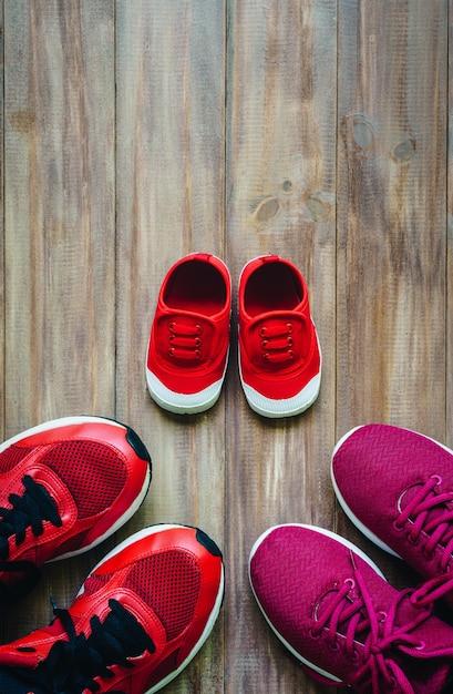 Trois chaussures de course de sport rouges ou espadrilles de mère et père et enfant Photo Premium
