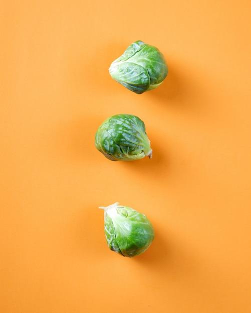 Trois chou vert sur une surface orange Photo gratuit