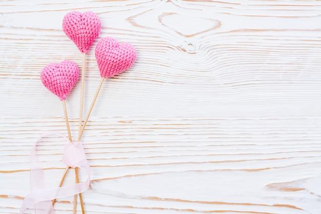 Trois coeurs tricotés roses avec ruban rose sur un fond en bois blanc Photo Premium