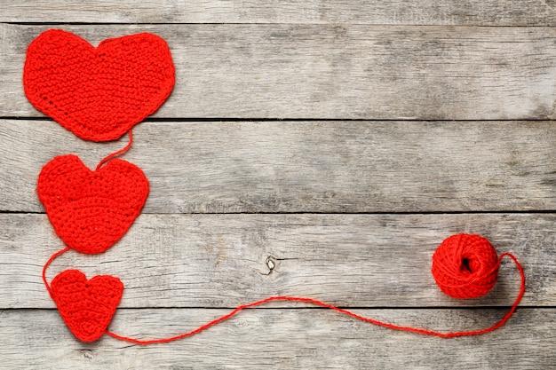 Trois coeurs tricotés rouges, symbolisant l'amour et la famille. relation familiale, liens. Photo Premium