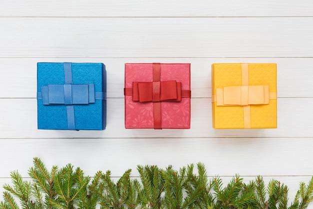 Trois coffrets cadeaux sur bois blanc avec une branche d'arbre de noël. vue de dessus Photo Premium