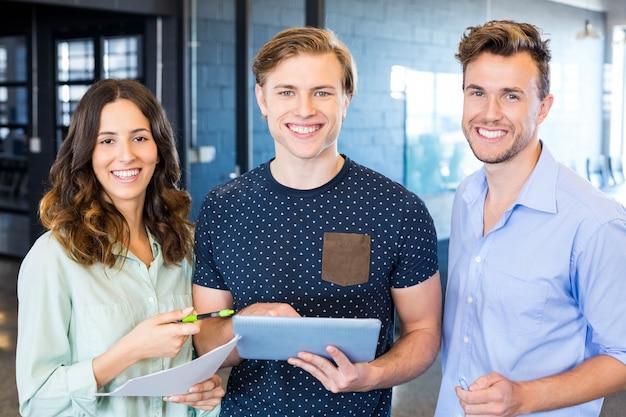 Trois collègues confiants discutant au bureau avec des documents et une tablette Photo Premium