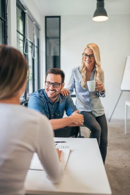 Trois collègues dans un espace de coworking ou une salle de classe moderne parlant et souriant. Photo Premium