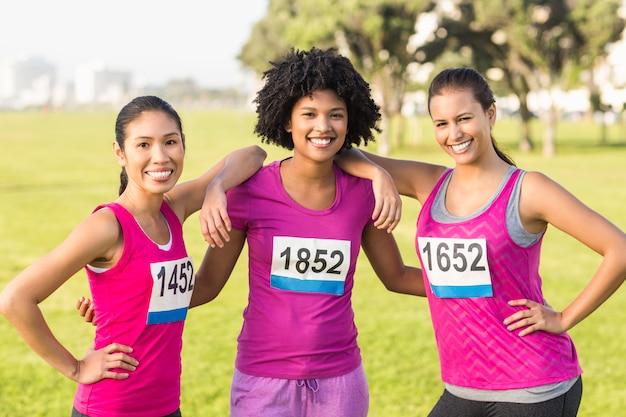 Trois coureurs souriants soutenant le marathon du cancer du sein Photo Premium