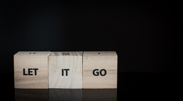 Trois cubes en bois dans une rangée - laissez-le aller Photo Premium