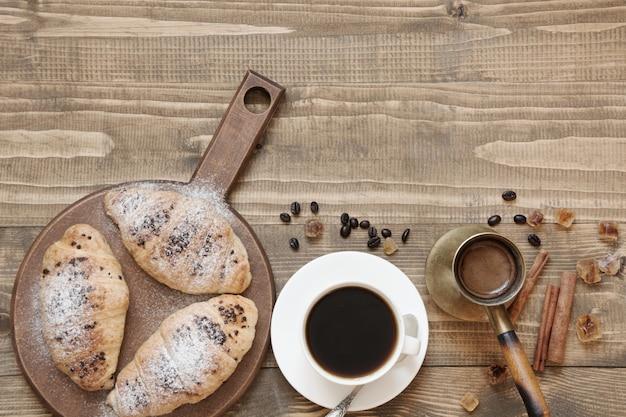 Trois délicieux croissants fraîchement sortis du four et une tasse de café sur une planche de bois. vue de dessus. petit déjeuner. espace de copie. Photo Premium