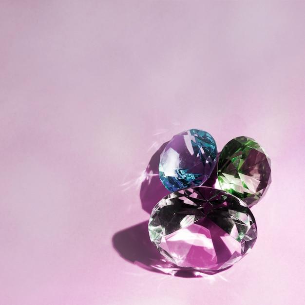 Trois diamants brillants luxueux sur fond rose Photo gratuit