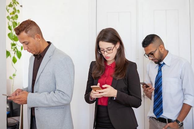 Trois employés de bureau concentrés sur les smartphones Photo gratuit