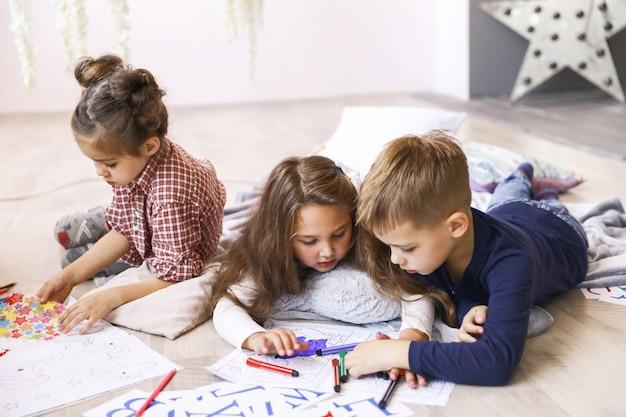 Trois enfants concentrés jouent sur le sol et dessinent dans des livres à colorier Photo gratuit
