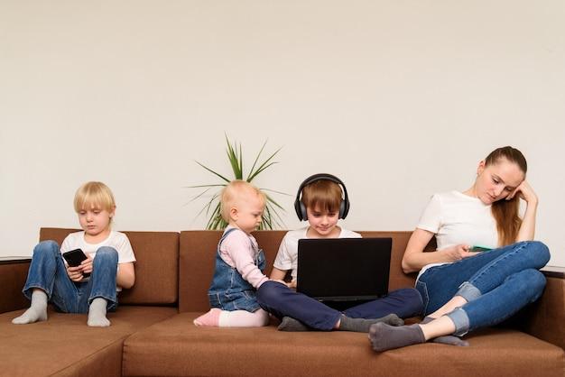 Trois Enfants Et Maman Assis à Côté D'utiliser Un Ordinateur Portable Et Un Téléphone. Addiction à Internet. Photo Premium