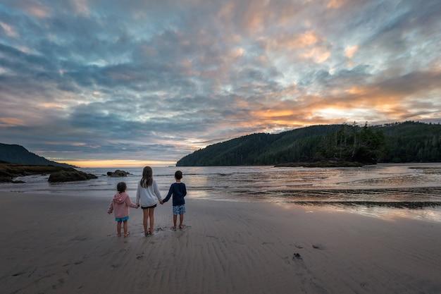 Trois Enfants Se Tenant La Main à La Voiture Au Beau Coucher De Soleil Sur Une Plage Appelez La Plage De La Baie De San Joseph Sur L'île De Vancouver En Colombie-britannique, Canada Photo Premium
