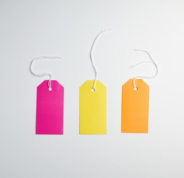 Trois étiquettes de papier de couleur sur une corde blanche Photo Premium