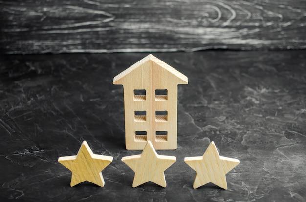 Trois étoiles en bois et une maison. hôtel trois étoiles ou restaurant. examen de la critique. Photo Premium