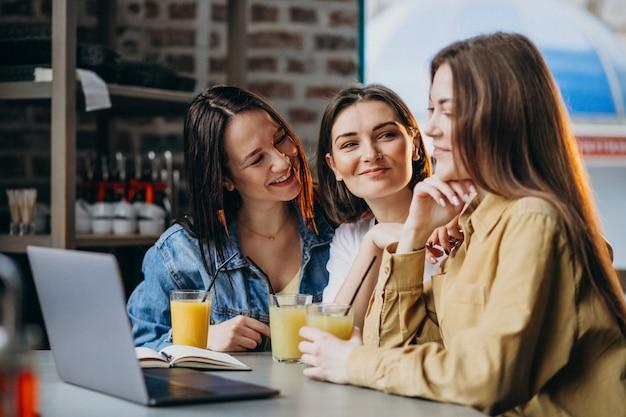 Trois étudiants Se Préparant à L'examen Avec Un Ordinateur Portable Dans Un Café Photo gratuit