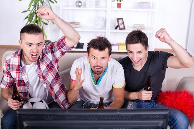 Trois fans de sport regardent un match à la télévision à la maison. Photo Premium