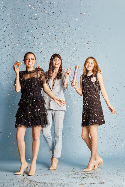 Trois femmes célèbrent des vacances en s'amusant avec des confettis Photo Premium