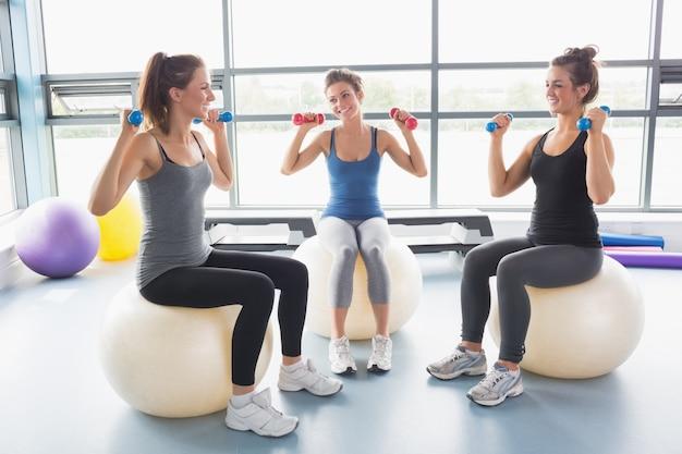 Trois femmes soulevant des poids sur des balles d'exercice Photo Premium