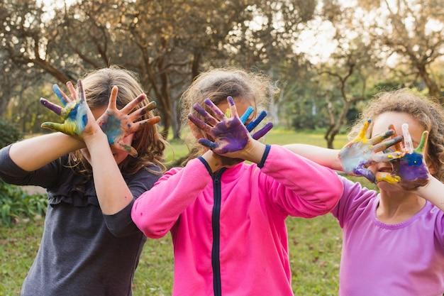 Trois filles couvrant leurs visages avec des paumes peintes Photo gratuit