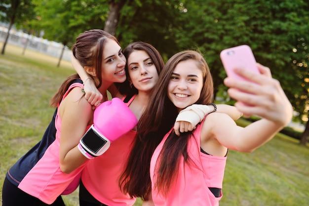 Trois filles de fitness prennent des photos d'eux-mêmes sur un appareil photo smartphone Photo Premium
