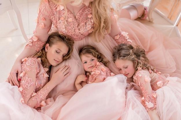 Trois filles en robes roses dorment sur les genoux de maman Photo gratuit