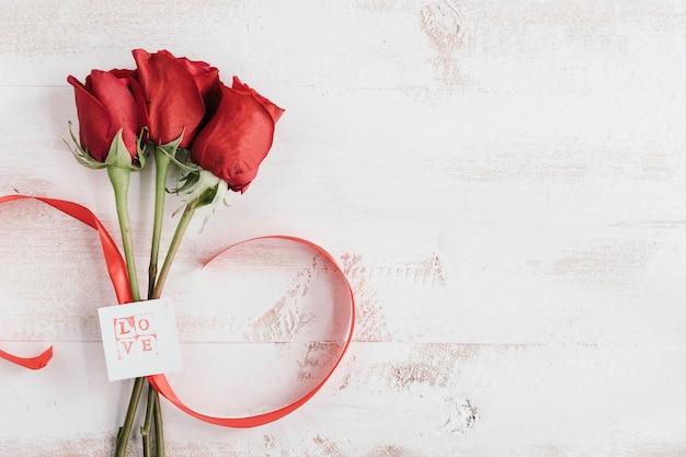 Trois Fleurs Rouges Avec Carte D'amour Et Espace Copie Photo gratuit