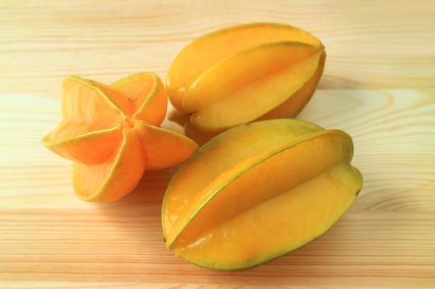 Trois fruits entiers mûrs jaunes vif de star fruit isolé sur une table en bois naturel Photo Premium