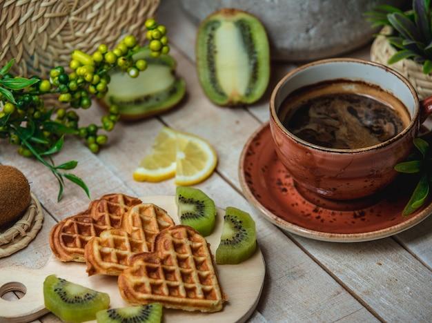 Trois gaufres en forme de coeur avec des fruits et une tasse d'espresso Photo gratuit