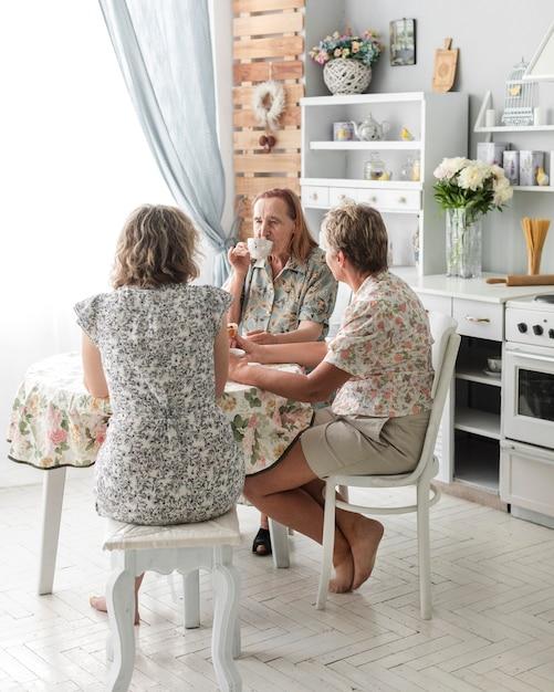 Trois générations de femmes buvant du café ensemble dans la cuisine Photo gratuit