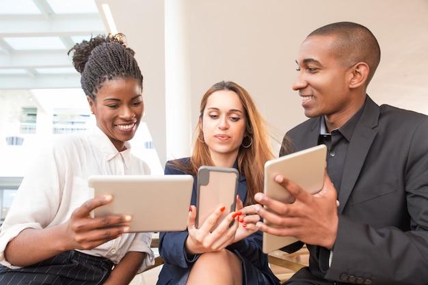 Trois hommes d'affaires heureux à l'aide de gadgets au bureau Photo gratuit
