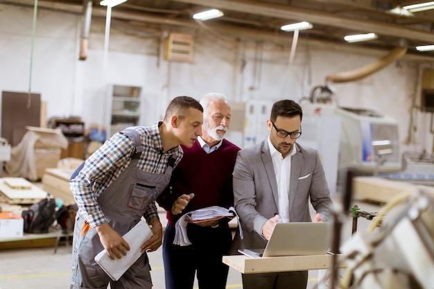 Trois hommes debout et discutent dans une usine de meubles Photo Premium