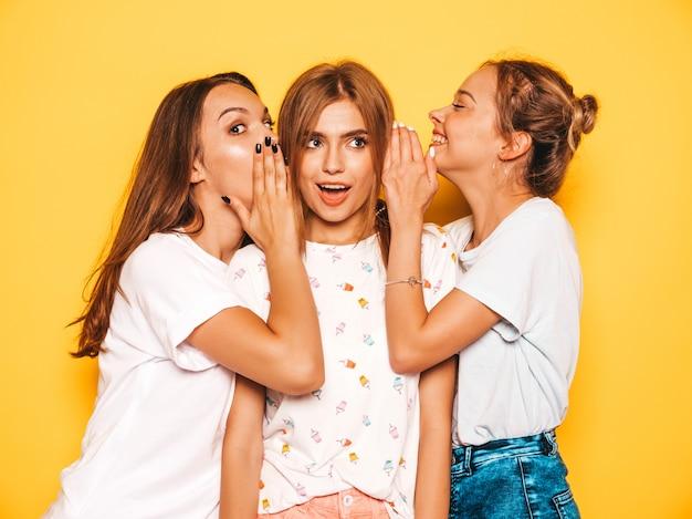 Trois Jeunes Belles Filles Hipster Souriantes Dans Des Vêtements D'été à La Mode. Femmes Insouciantes Sexy Posant Près Du Mur Jaune. Les Mannequins Positifs Deviennent Fous Et S'amusent. Photo gratuit