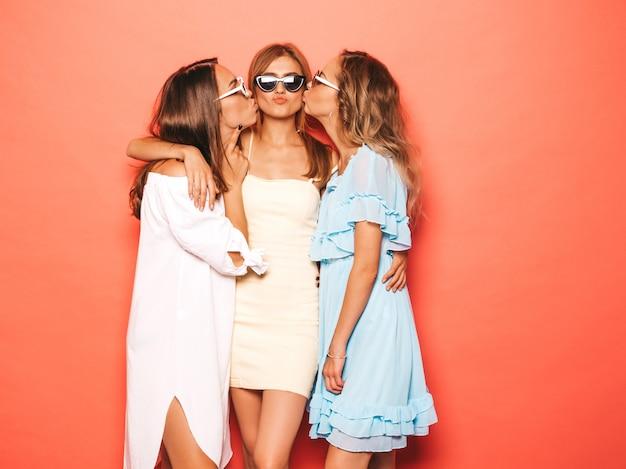 Trois Jeunes Belles Filles Hipster Souriantes Dans Des Vêtements D'été à La Mode. Femmes Insouciantes Sexy Posant Près Du Mur Rose. Des Mannequins Positifs Deviennent Fous Et S'amusent En Embrassant Leur Ami Dans La Joue Photo gratuit