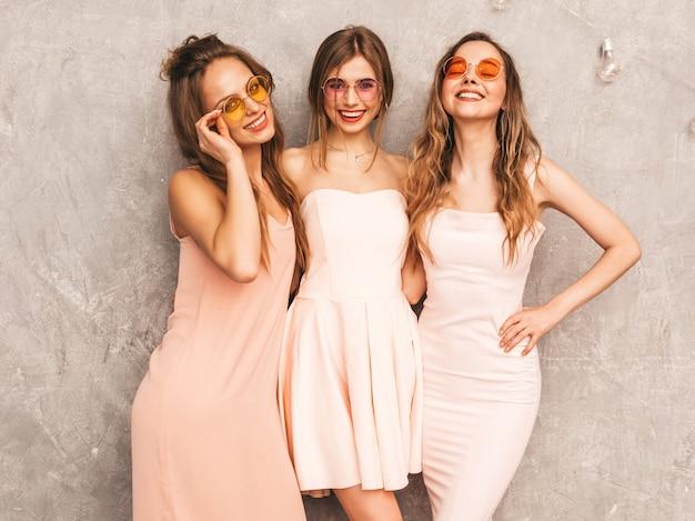 Trois Jeunes Belles Filles Souriantes Dans Des Robes Rose Pâle D'été à La Mode. Femmes Insouciantes Sexy Posant. Modèles Positifs En Lunettes De Soleil Rondes S'amusant Photo gratuit