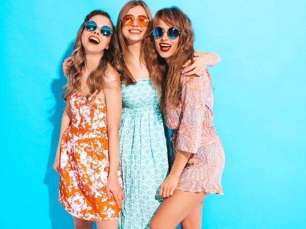 Trois Jeunes Belles Filles Souriantes En Robes Décontractées D'été à La Mode Et En Lunettes De Soleil. Femmes Insouciantes Sexy Posant. Photo gratuit