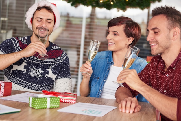 Trois Jeunes Buvant Du Champagne Au Bureau Photo gratuit