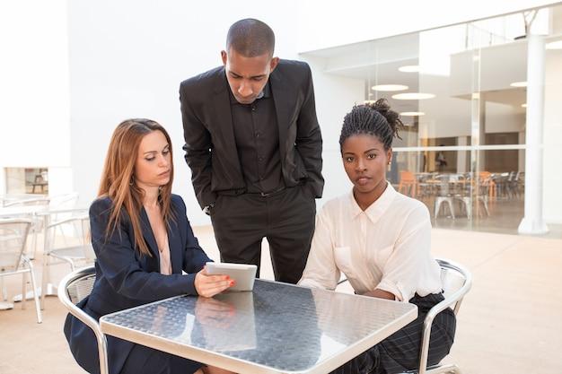 Trois jeunes collègues sérieux discutant au café Photo gratuit