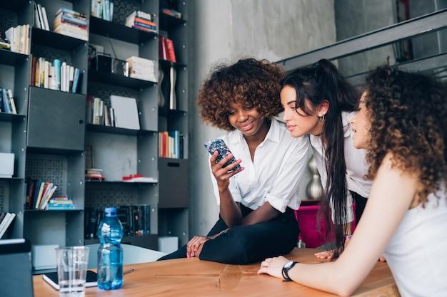 Trois jeunes femmes multiraciales à la recherche d'un smartphone dans un bureau moderne co-working Photo Premium