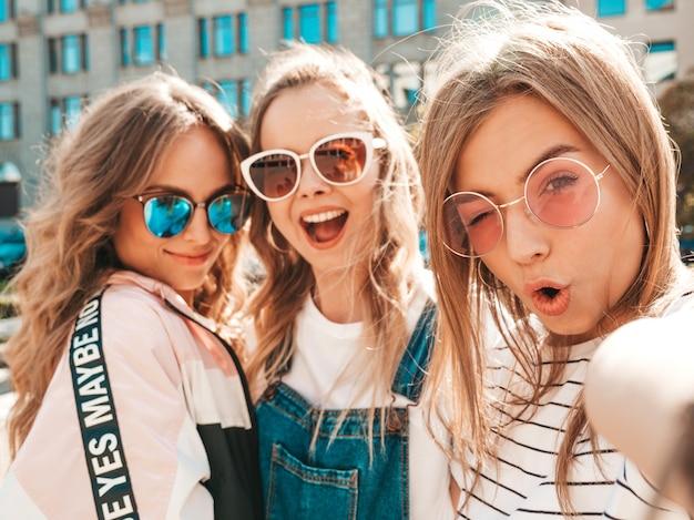 Trois Jeunes Femmes Souriantes Hipster Dans Des Vêtements D'été.filles Prenant Des Photos D'autoportrait Selfie Sur Smartphone.modèles Posant Dans La Rue.femme Montrant Des émotions Positives Photo gratuit