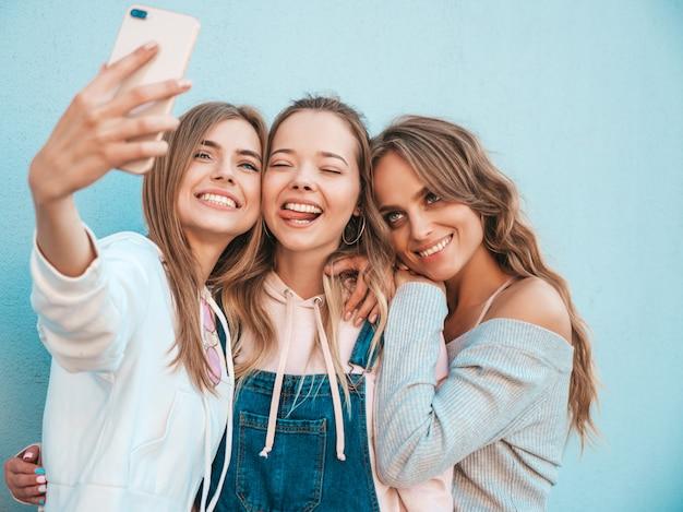 Trois Jeunes Femmes Souriantes Hipster En Vêtements D'été.filles Prenant Des Photos D'autoportrait Selfie Sur Smartphone.modèles Posant Dans La Rue Près Du Mur.femme Montrant Des émotions Positives. Photo gratuit