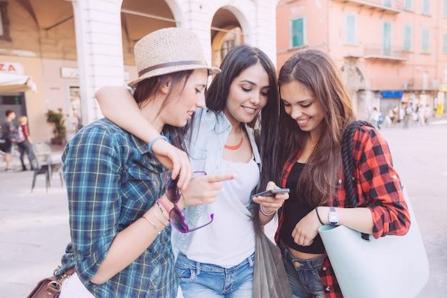 Trois jeunes femmes avec un téléphone intelligent dans la ville Photo Premium
