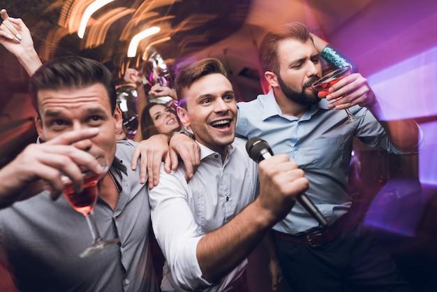 Trois jeunes hommes chantent dans un club de karaoké Photo Premium