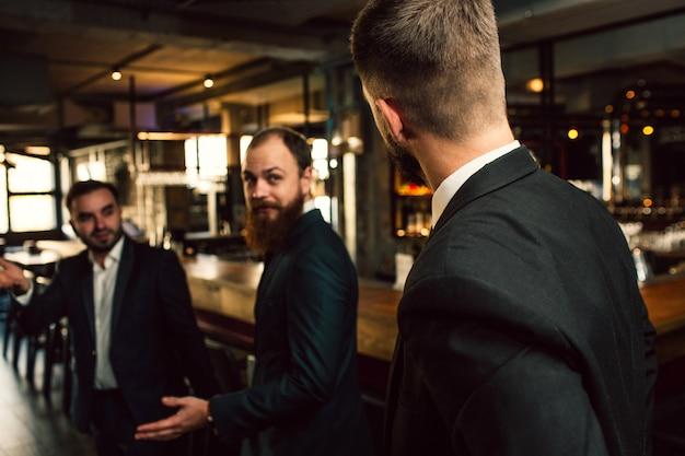 Trois Jeunes Hommes En Costume Se Regardent. L'un D'eux Se Tient Dos à La Caméra. Les Employés De Bureau Se Tiennent Dans Un Pub. Photo Premium