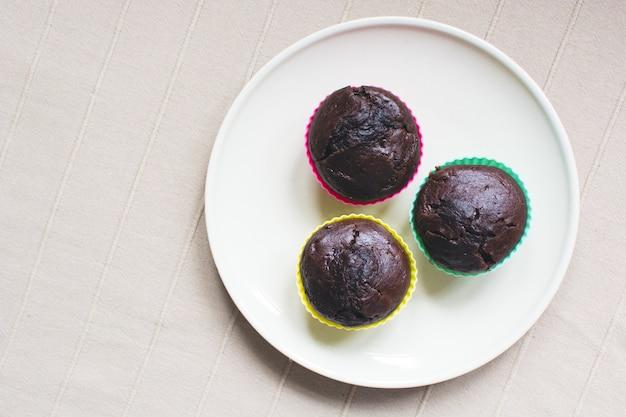 Trois muffins chocholate sur une plaque aérienne Photo gratuit