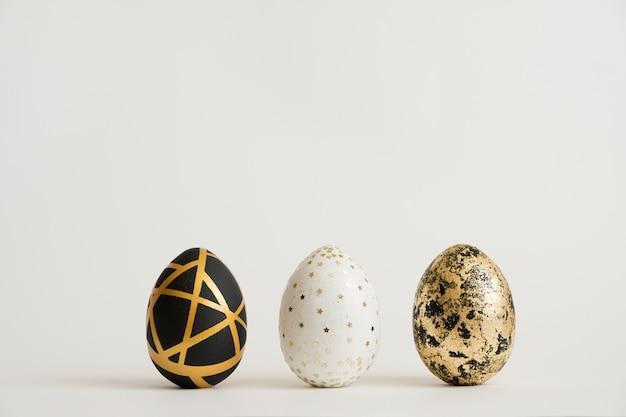 Trois oeufs décorés en or de pâques. concept de pâques minimal Photo Premium
