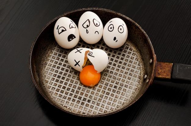 Trois oeufs avec émotions, oeuf cassé au centre de la casserole, tableau noir Photo Premium