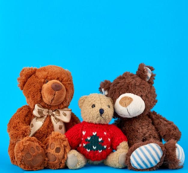 Trois ours en peluche sur un fond bleu, concept d'amitié Photo Premium