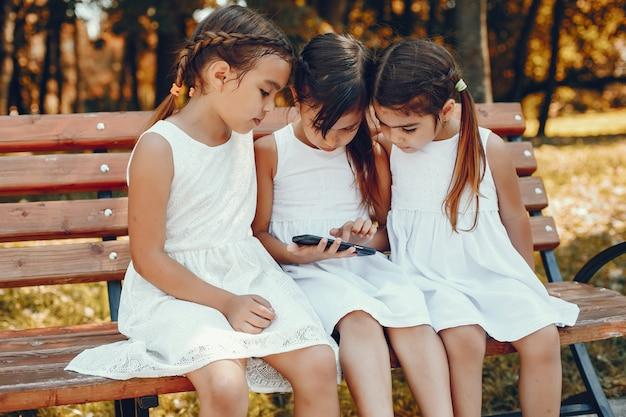 Trois petites soeurs assises dans un parc d'été Photo gratuit