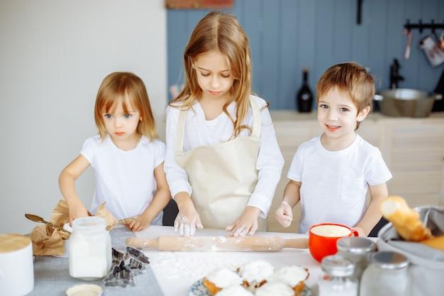 Trois petits chefs profitant dans la cuisine pour faire de gros dégâts Photo Premium
